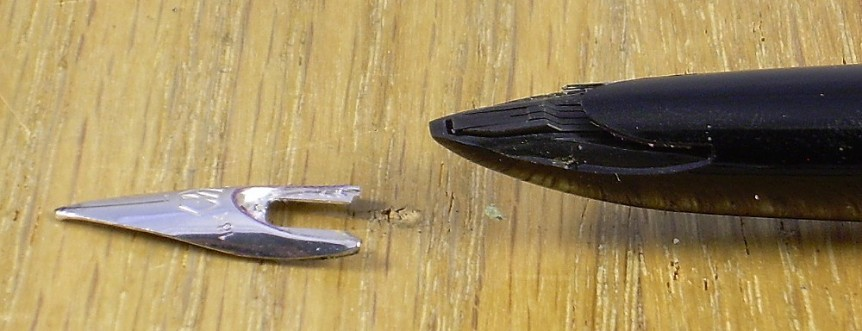 Fountain pen with its point separated from it. The point is shaped like an Isosceles triangle, with rounded edges on the long sides, and a rectangular cutout intruding into the base. It is made to slot into the body of the pen.