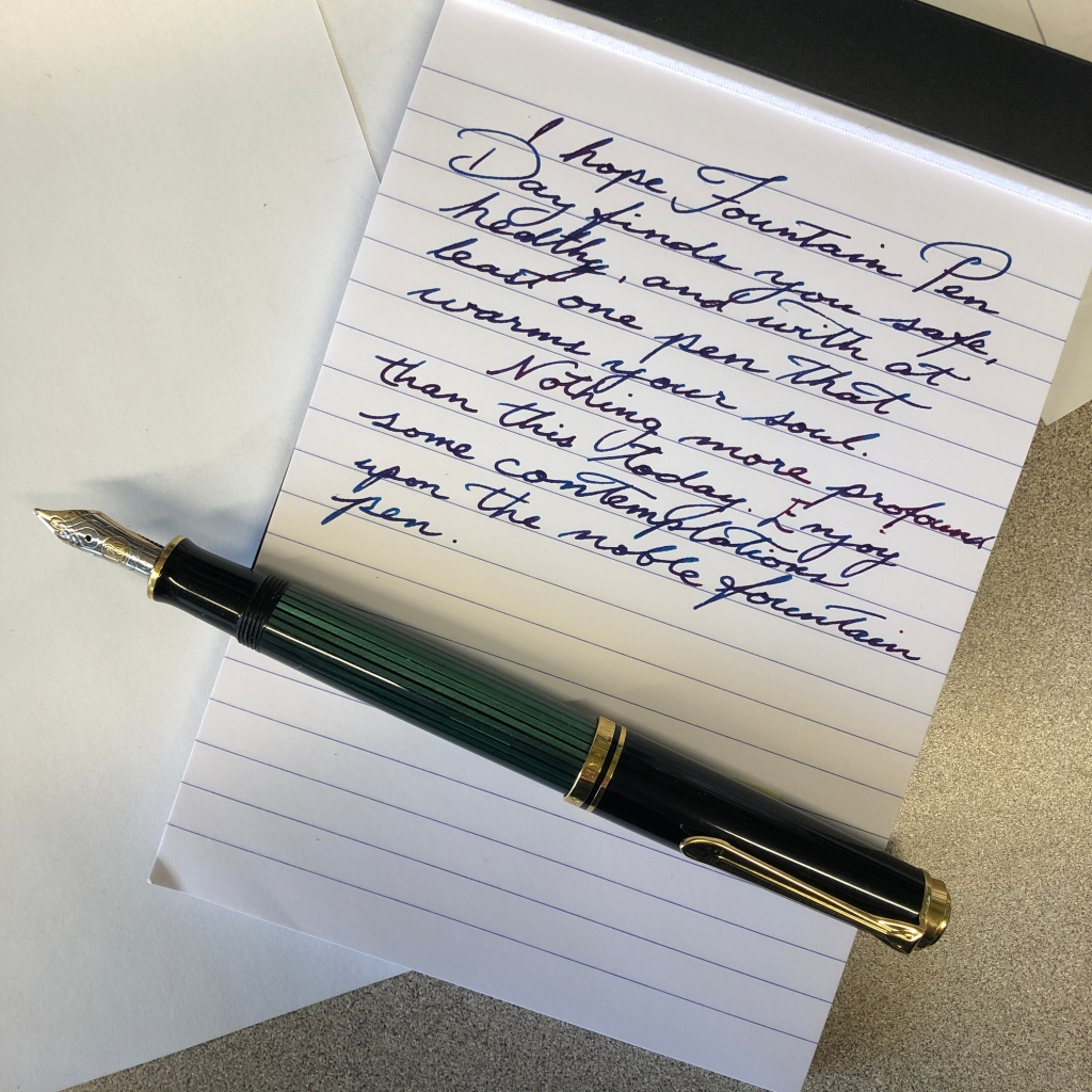 """A fountain pen, the cap off, lies upon a note pad. On the pad, this message:  """"I hope Fountain Pen Day finds you safe, healthy, and with at least one pen which warms your soul.  """"Nothing more profound than this today. Enjoy some contemplation upon the noble fountain pen."""""""